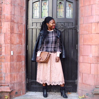 Magazine writer and editor Busola Evans poses in front of a door wearing a pink skirt and black leather jacket.