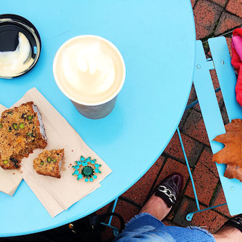 A slice of cake and a takeaway capuccino on a table outside a cafe