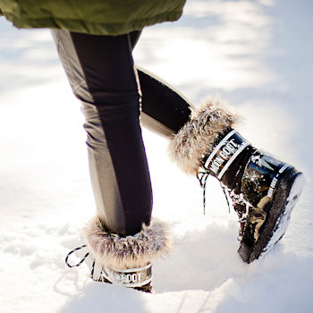 A woman pictured walking in the snow wearing a faux fur trimmed snow boot