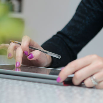 Woman pictured using Ipad, close up on hands and screen
