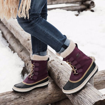 Woman standing on a snow covered log wearing Sorel Winter Carnival snow boot