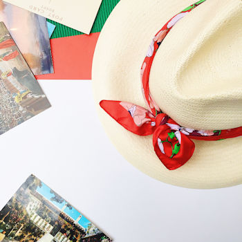 A panama hat is pictured from above alongside postcards