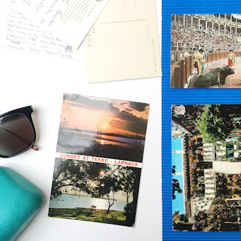 Vintage postcards from Spain and Germany pictures next to a pair of sunglasses