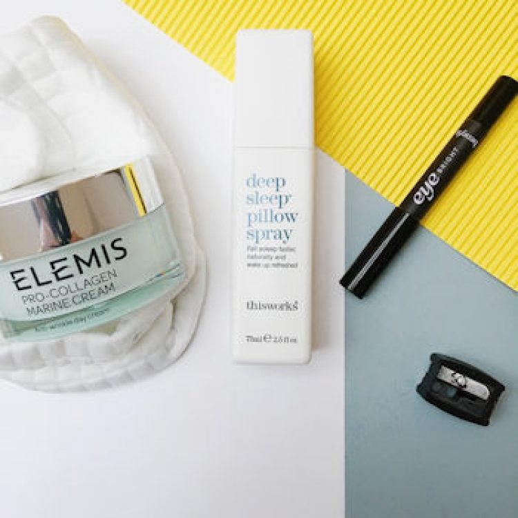 A pot of Elemis face cream, This Works Deep Pillow Spray, and Benefit Eye Bright pencil on a white yellow and grey background