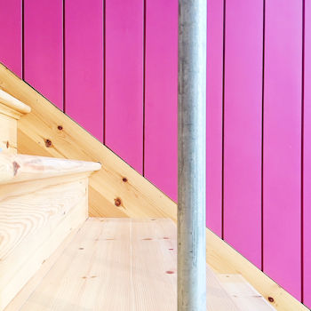 Stairs and a pink panelled wall