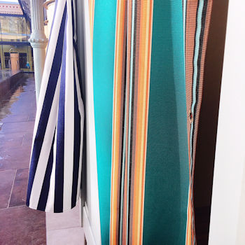 Striped curtains blow in the wind by a swimming pool