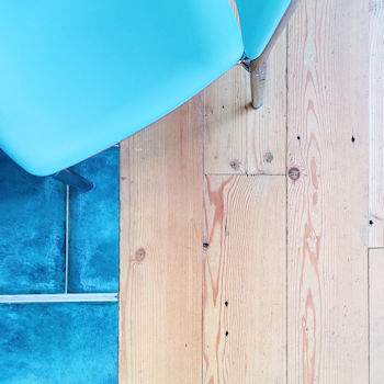 Blue chair pictured from above, wooden floor and blue tiles