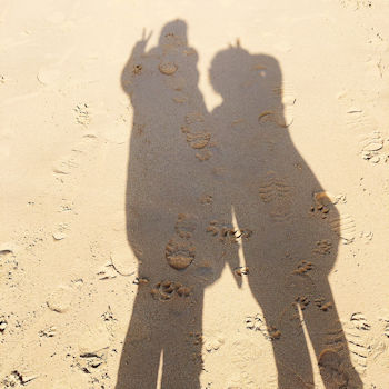 Shadows of two people on Watergate Bay Beach in Cornwall