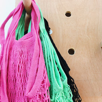 Brightly coloured string shopping bags at Tinker Tailor shop
