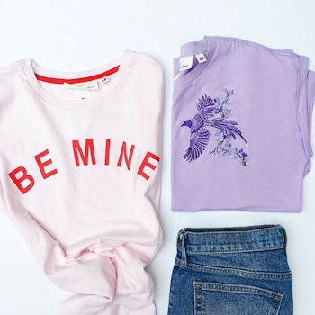 Pink 'Be Mine' and purple bird t-shirts by H&M, flat lay photograph with jeans, denim and tee