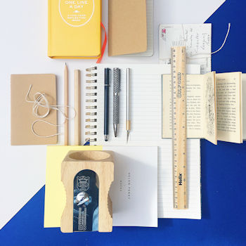 A staionary flat lay image, including a wooden ruler, notepads, pens and pencils on a blue and white background.