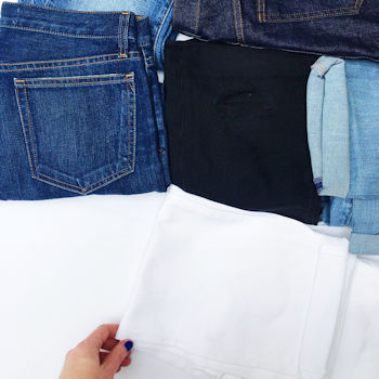 A flat lay image of ladies jeans. A mix of blue, black and white denim.