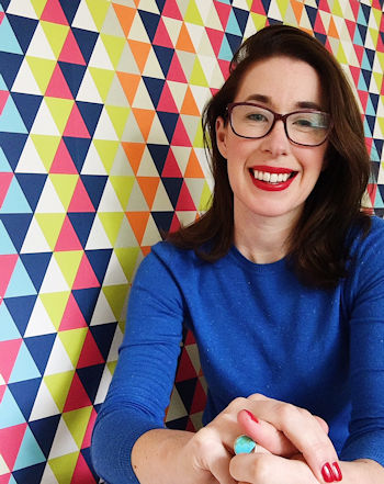 Journalist and blogger Helen Perry, Harlequin wallpaper, blue jumper, red lipstick