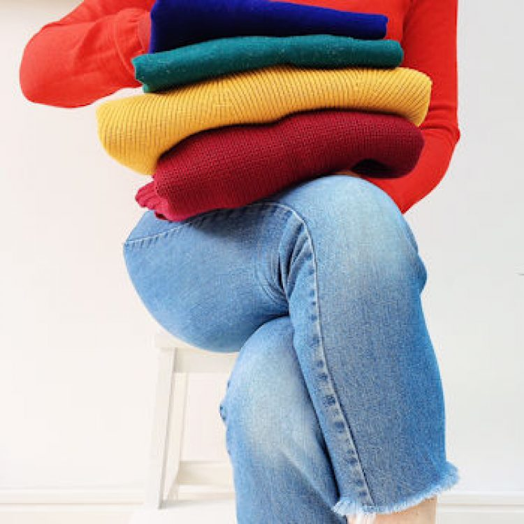 Woman sits on a white stool wearing jeans and holding a pile of colourful sweaters