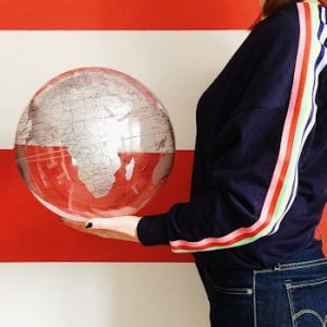 Me balancing a globe on my hand in front of a red and white striped wall