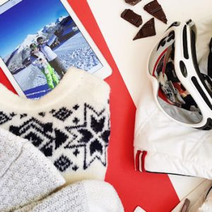A flat lay including a pair of ski goggles and a photograph of two women on a mountain