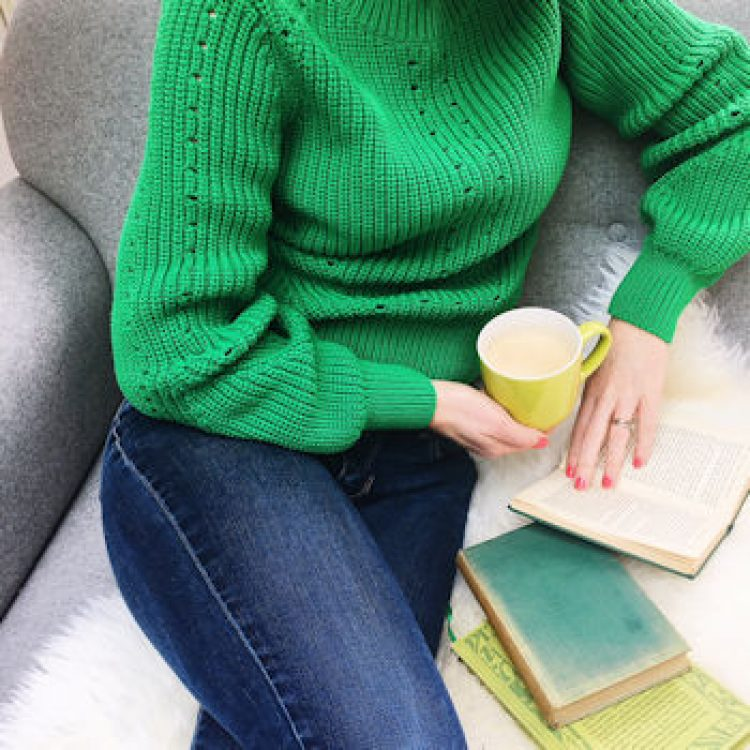 The ups and downs of working from home. A photograph by Helen Perry. Green jumper, grey sofa, jeans.