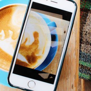 A cappuccino pictured on an iPhone, resting on a cappuccino
