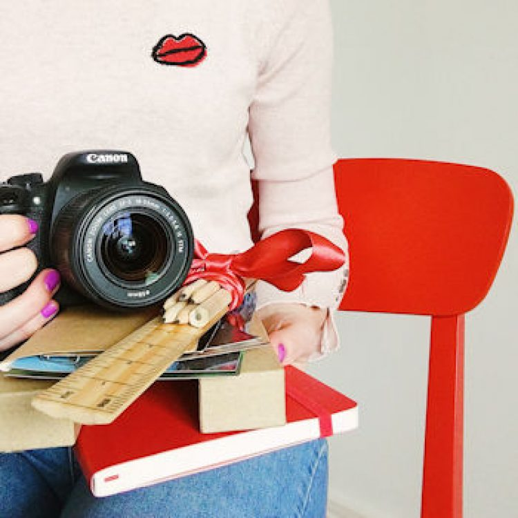 Helen Perry, journalist and blogger, Canon camera, red chair, lips jumper