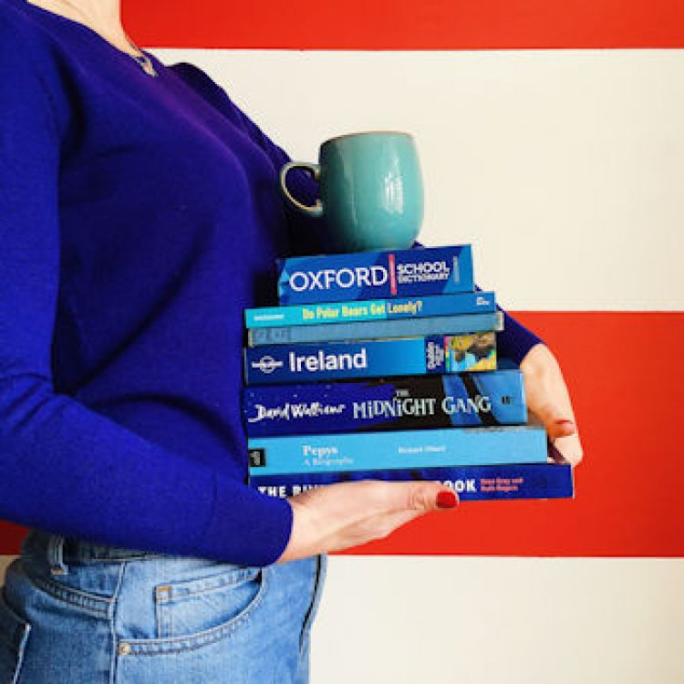 Person in blue jumper carrying a pile of blue books with a mug balanced on top